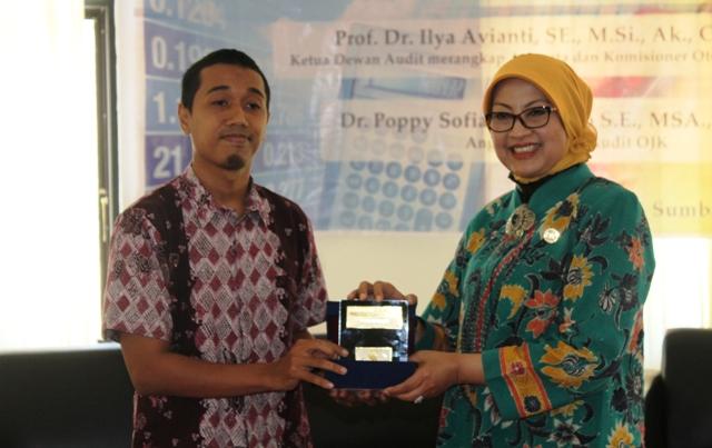 Dekan Fakultas Ekonomi UTS, Abdul Hadi Ilman MPP menyerahkan cinderamata kepada Ketua Dewan Audit sekaligus Komisioner OJK, Prof Dr Ilya Avianti, SE, M.Si, Ak, CPA, CA