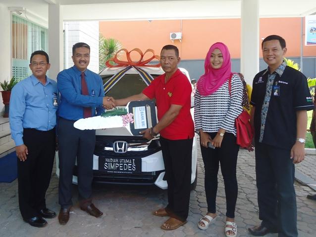 Pimpinan BRI Cabang Sumbawa, Anis Abdul Hakim didampingi dua AMMB, menyerahkan mobil Honda Mobilio SMT kepada Hasanul Basri, Nasabah BRI Unit Kota I pemenang utama undian Simpedes 2015