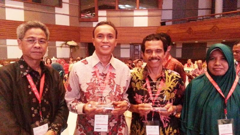 Kepala Arpusda Sumbawa, H Syahril S.Pd M.Pd menunjukkan trofi penghargaan Pengembangan Perpustakaan
