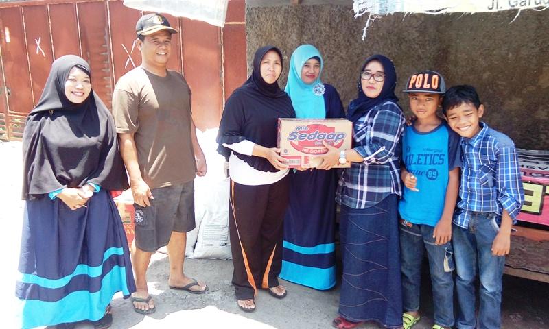Nurmala dari Posko Korban Banjir Karang Bage didampingi Hermansyah S.Pd ketua RT setempat, menerima bantuan secara simbolis dari ibu-ibu warga Desa Sekongkang Bawah KSB