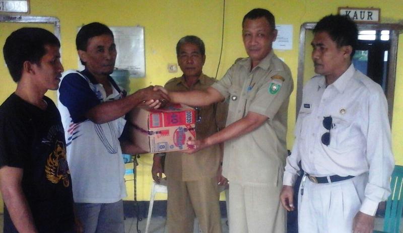 Camat Plampang, Ir. Nawawi menyerahkan bantuan kepada korban banjir