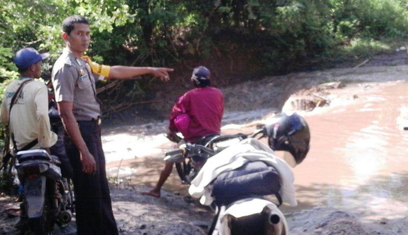 petugas Babhinkamtibmas Desa Prode, Bripka Darmawan turun tangan. Ia berdiri di pinggir sungai menghalau dan memperingatkan warga untuk tidak menyeberang.